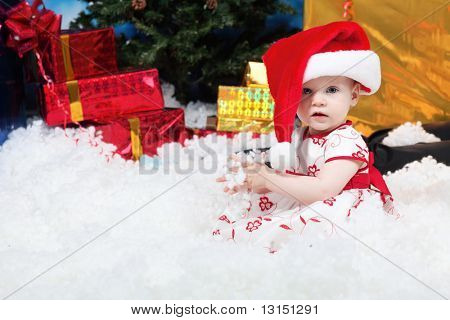 Christmas child sitting in snowdrift against night stellar sky.