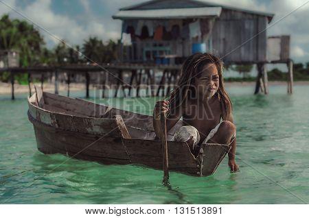 Maiga Island Sabah Malaysia - April 29 2016 : Little girl paddling a wooden boat in Maiga Island Sabah Malaysia.