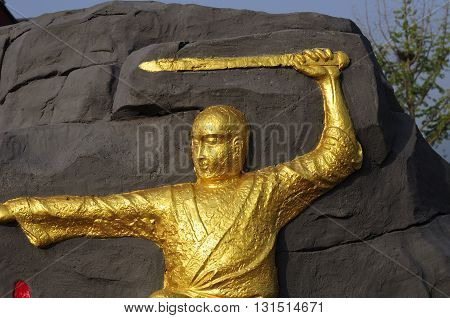 A gold carving of a shaolin monk holding a sword at the Shaolin Temple scenic area in Dengfeng city Henan province China.