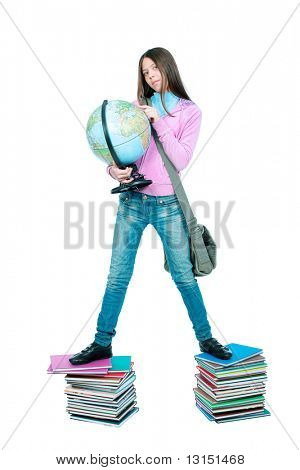 Portrait of a schoolgirl standing on a stack of books with her globe.