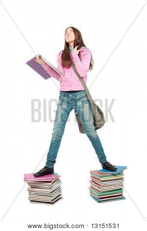 Portrait of a scoolgirl standing on a stack of books.