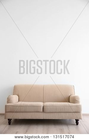 Cozy couch on wall background