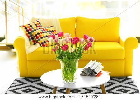 Beautiful fresh tulips on round table
