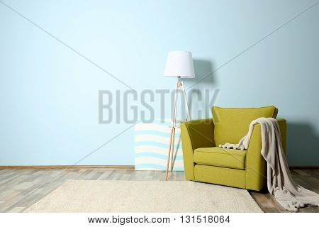 Room interior with green armchair on blue wall background