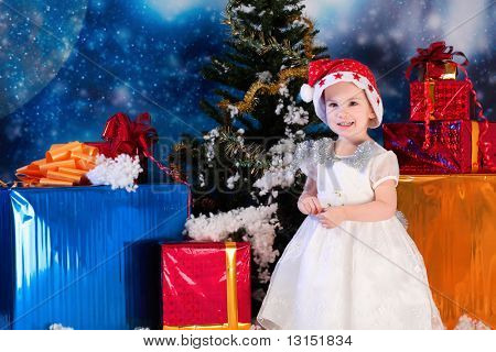 Christmas child standing with presents against night stellar sky.