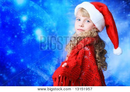 Christmas kid in Santa hat over stellar sky.
