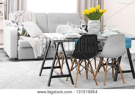 Dining room interior with sofa and table served for dinner