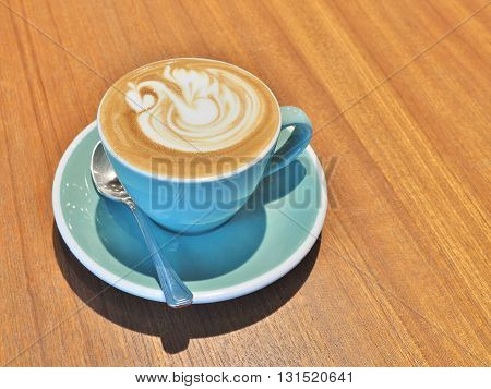 Cup of hot coffee with swan shape latte art on wooden background.