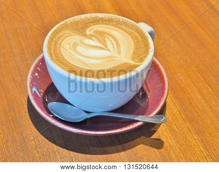 Cup of hot coffee with heart pattern latte art in a white cup on wooden background.