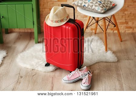 Red suitcase with gumshoes and hat indoors
