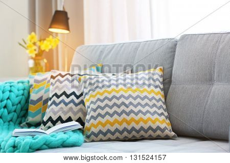 Stylish pillows on grey couch in room interior