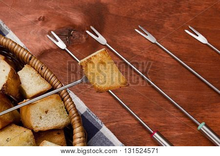 Characteristic forks used for fondue on a wooden background