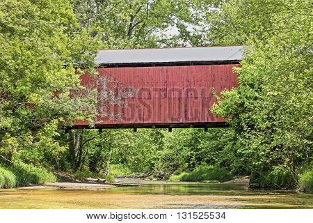 The red Wilkins Mill Covered Bridge built in 1906 crosses Sugar Mill Creek in historic Parke County Indiana.