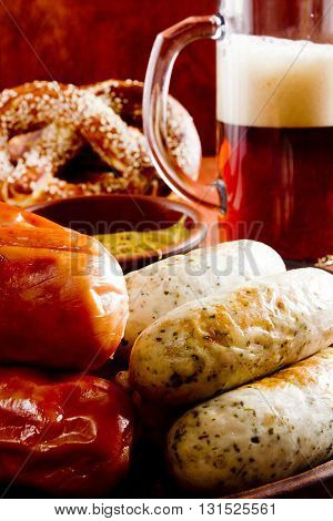 Traditional sausages pretzels and beer on a wooden background