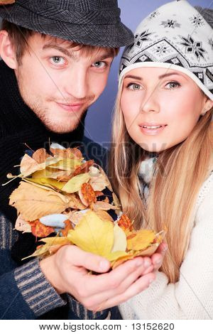Portrait of a young couple in autumn clothes with leaves in their hands.