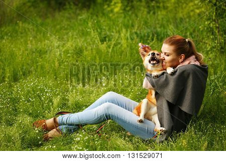 Girl kissing dog Shiba Inu in Spring Park. Walking with a pet. Pedigree dog. Walking dogs. Dog happiness.