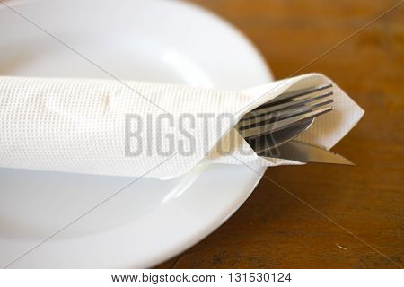 Fork knife and spoon on a plate with napkin