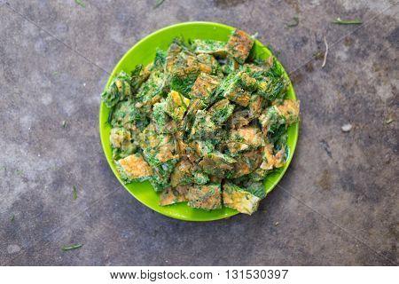 Thai Cuisine; cha-om omelet in green plate