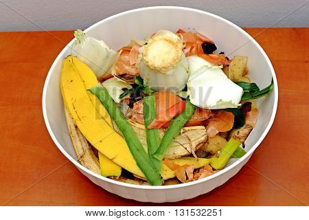 Vegetable scraps in a white plastic bowl bio waste carrots cesium potato peels leek