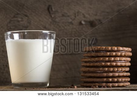 One glass of milk with stack of chocolate biscuits on old wooden table