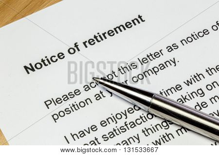 Notice of retirement letter closeup with a silver pen on a wooden table