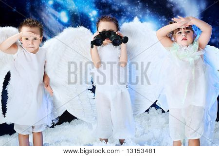 Beautiful little angels looking through a binocular,  snowy background.