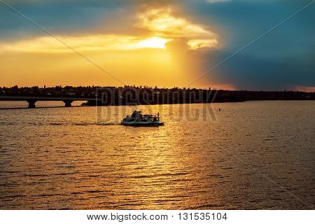 golden sunset in dramatic sky over river with boat