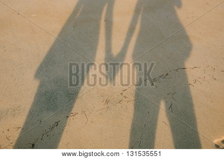 shadow of lovers holding hands at heart on the beach.