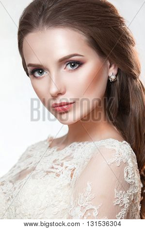 Beauty model girl with perfect make-up isolated over white. Portrait of attractive young woman with dark hair on white background. Beautiful female face with clear fresh skin.