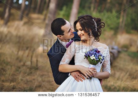 the couple in the pine forest, looking at each other. Love and happy husband and wife.