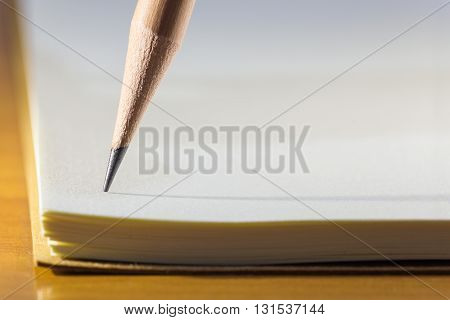 Close up of pencil's tip on blank white notebook paper with long skinny shadow on wooden table selective focus on the tip of pencil