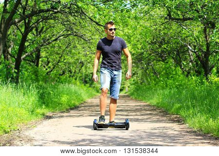 man riding hoverboard - electrical scooter, personal eco transport, smart balance wheel