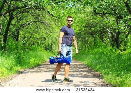 young man carrying sport bag with electrical scooter - hoverboard, portable eco transport