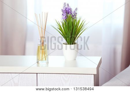 Handmade reed freshener with flower on white commode in living room, close up