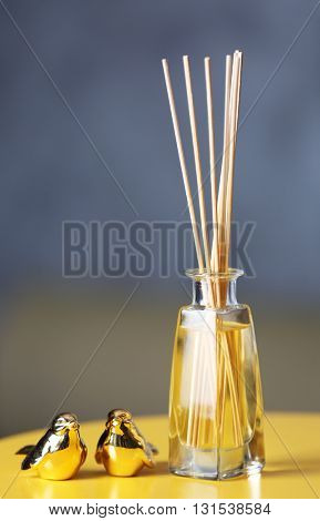 Handmade reed freshener on yellow table, close up