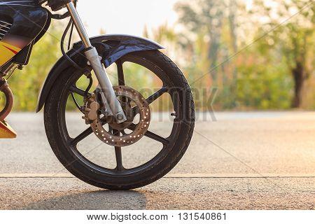Close up front wheel of motorbike on asphalt road
