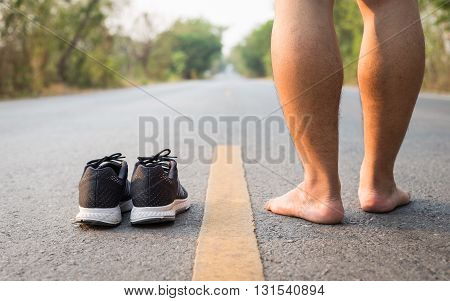 Legs Of Man With Black Running Shoes On Asphalt Road In Morning Time