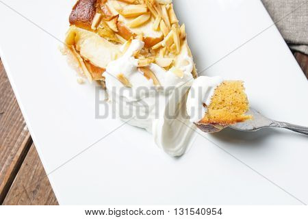 Apple tart. Pie with almonds and sour cream served on a white plate