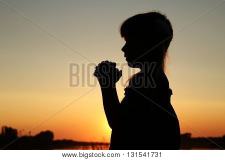 nice silhouette of a little girl praying