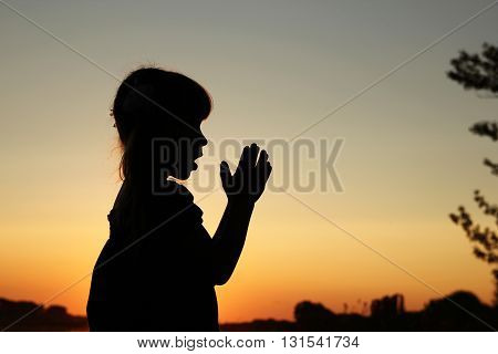 a nice silhouette of a little girl praying