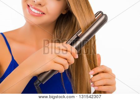 Close up portrait of smiling girl with long hair using a straightener
