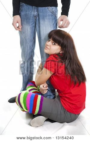 Nice Girl Sits Having Embraced A Foot Of The Guy