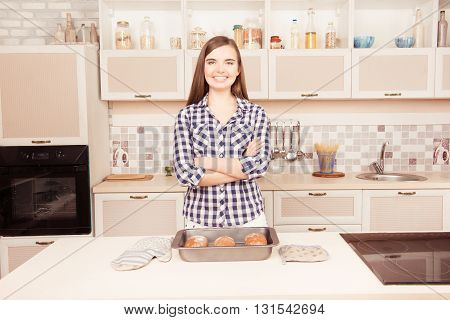 Attractive Happy Girl With Crossed Hands In The Kitchen With Baked Bread