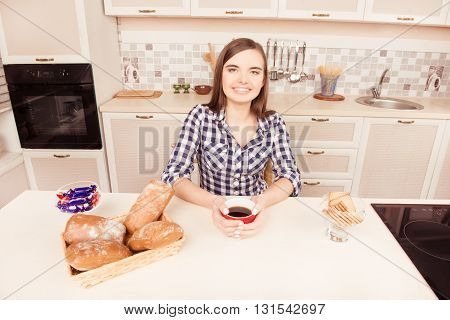 Young Girl Sitting In The Kitchen And Eatind Bun With Tea