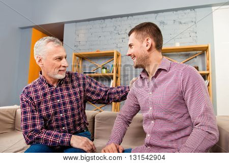 Father And Son Sitting On Couch And Having Funny Talk