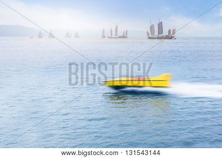 a yellow speedboat sailing on the city lake against blue sky