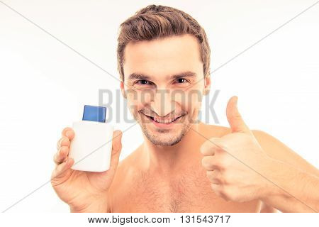 Handsome Young Man Holding Lotion After Shave Showing Thumb Up