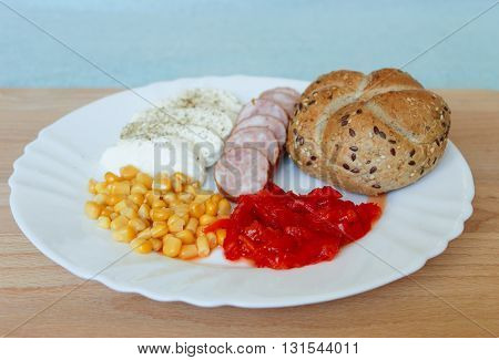 cold supper on white plate mozzarella sliced sausage with bun corn and pickled peppers