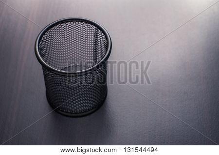 Metal basket for pencil on wooden background