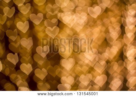 Blurring lights bokeh background of golden hearts